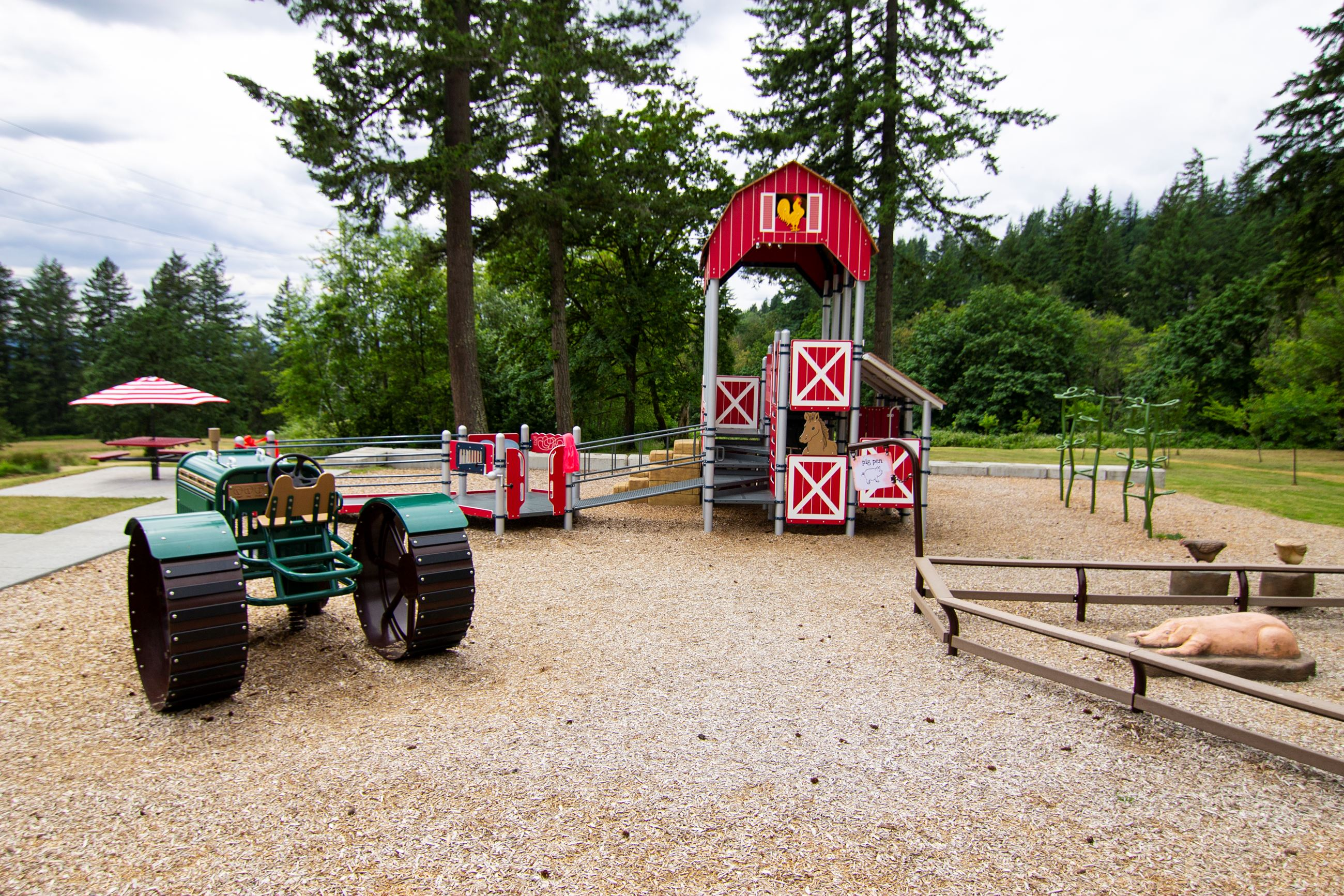 Park with farm playground structures (tractor, barn, pig sty)