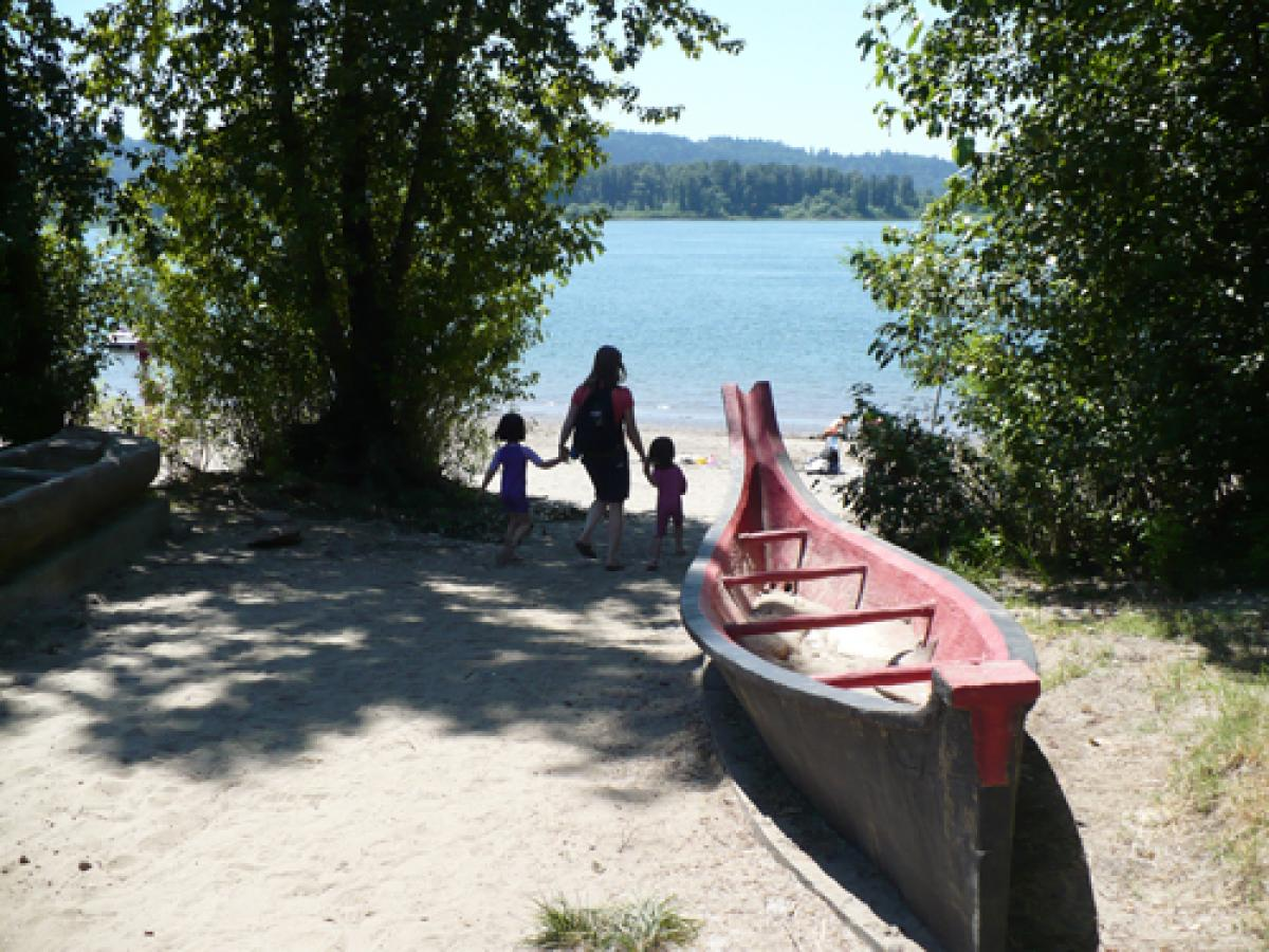 Woman with two kids walking toward the beach, models of canoes in the foreground